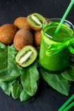 Green smoothie near ingredients for it on black wooden background. Kiwi and spinach. Detox. Healthy drink. Stock Photos