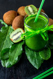 Green smoothie near ingredients for it on black wooden background. Kiwi and spinach. Detox. Healthy drink. Stock Photography