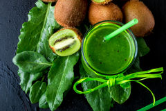 Green smoothie near ingredients for it on black wooden background. Kiwi and spinach. Detox. Healthy drink. Top view. Royalty Free Stock Images