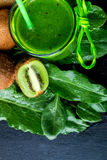 Green smoothie near ingredients for it on black wooden background. Kiwi and spinach. Detox. Healthy drink. Top view. Stock Photo