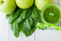 Green smoothie near ingredients for it on white wooden background. Apple, lime, spinach. Detox. Healthy drink. Green smoothie near ingredients for it on white royalty free stock photography