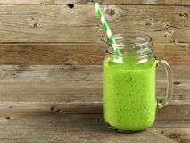 Green smoothie on old wood background. Healthy green smoothie in a mason jar mug on old wood Stock Photo