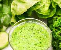 Green smoothie over vegetables background Stock Image