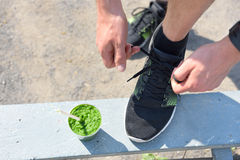 Green smoothie and running - healthy lifestyle. Closeup of male runner's sport shoe tying laces on park bench for diet and weight loss concept for men. Getting Royalty Free Stock Image