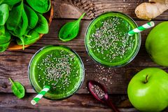 Green smoothie with spinach, apple, ginger  and chia seeds on a wooden background. top view. Healthy green smoothie with spinach, apple, ginger and chia seeds on Royalty Free Stock Photography