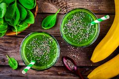 Green smoothie with spinach, banana and chia seeds on a wooden background. top view stock photo