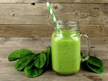 Green smoothie with spinach on wood. Healthy green smoothie with spinach in a jar mug against a wood background Stock Photo