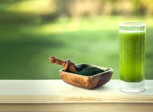 Green smoothie with spirulina on wood background.  stock images