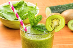 Green smoothie with a straw and fresh ingredients Royalty Free Stock Images