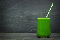 Green smoothie with straw on a slate background Royalty Free Stock Photo