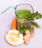 Green Smoothie top view. Green smoothie with carrot, lemon, parsley and ginger, top view Stock Images