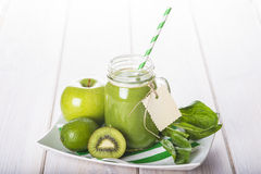 Green smoothie on a white wooden background Royalty Free Stock Photo