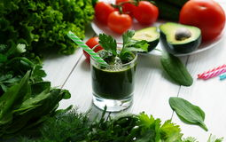 Green smoothies avocado. Cucumber and fresh herbs on a white wooden background Royalty Free Stock Photography