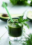 Green smoothies avocado. Cucumber and fresh herbs on a white wooden background Stock Photo