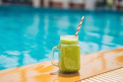 Green smoothies of spinach and banana on the background of the pool. Healthy food, healthy smoothies.  stock photos