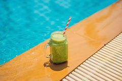 Green smoothies of spinach and banana on the background of the pool. Healthy food, healthy smoothies.  royalty free stock image