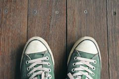 Green sneakers from an aerial view on wooden floors. Top view. Exploration Concept stock photos
