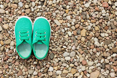 Green sneakers on a background of small stones stock image