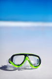 Green snorkel and waterproof mask lying on sand behind blue sky Stock Image