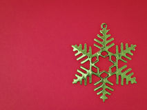 Green snowflake on red Royalty Free Stock Photography