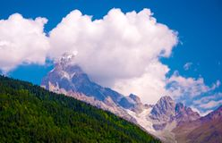 Green and snowy mountains, clouds and glacier in Georgia. Mountain landscape on sunny summer day royalty free stock photos
