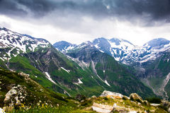 Green and snowy mountains with dark storm clouds above Stock Images