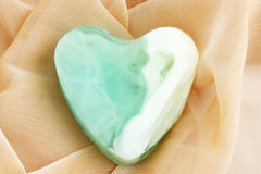 Green soap. Green  soap in the form of the heart  on the cloth Stock Photo