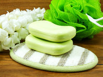 Green soap bar and plastic bath puff on wooden background Stock Photos