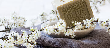 Green soap with olive oil over towel and fresh flowers Stock Image