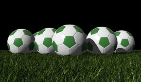 Green soccer balls on a green grass Royalty Free Stock Photography