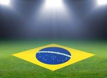 Green soccer field, brazil flag. Bright spotlights, illuminated stadium royalty free stock image