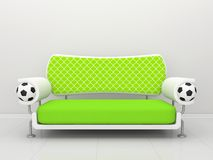 Green sofa with football symbolics Royalty Free Stock Photo