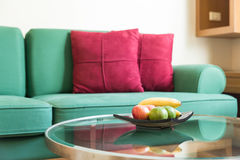 Green sofa with red backrest pillow Royalty Free Stock Photos