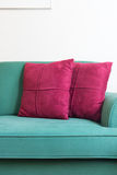Green sofa and red backrest pillow Royalty Free Stock Photo