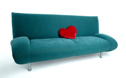 Green sofa with red heart. Shaped pillow lying on the middle of the couch stock photos