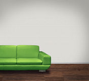 Green sofa in white room. Modern green leather sofa in room with dark floor and white walls Stock Photo