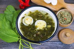 Green sorrel soup with egg. And spices on a wooden board stock photo