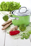 Green soup pot with Asian ingredients. Green pot with lime, ginger, fresh coriander and chili pepper. Asian style ingredients for Thai Tom Yam soup stock photo