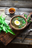 Green soup with sorrel in wooden bowl. Style rustic, wooden background. Selective focus Royalty Free Stock Photo