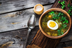 Green soup with sorrel in wooden bowl. Style rustic, wooden background. Selective focus Royalty Free Stock Photography