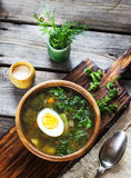 Green soup with sorrel in wooden bowl. Style rustic, wooden background. Selective focus Stock Photos