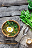 Green soup with sorrel in wooden bowl. Style rustic, wooden background. Selective focus Royalty Free Stock Image