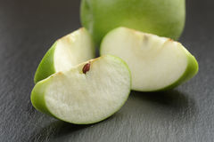Green sour apple on slate board sliced Royalty Free Stock Photos