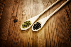 Soybeans and black beans in wooden spoons Royalty Free Stock Photos