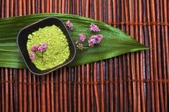 Green spa modder, violet bloem en blad op bruine mat stock afbeeldingen