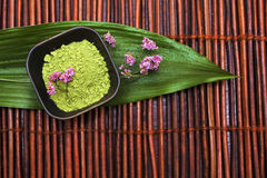 Green spa mud, violet flower and leaf on brown mat Stock Images