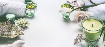 Green spa or wellness background with towels, candle, orchid flowers and body and face care tools and accessories on white desktop. Top view with copy space Royalty Free Stock Photo