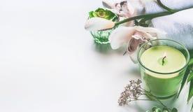 Green spa of wellnessachtergrond met handdoeken, kaars, orchideebloemen en toebehoren stock foto