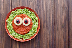 Green spaghetti creative pasta scary halloween food vampire monster with fake blood tomato sauce. And funny big mozzarella eyeballs decoration kid party meal on Stock Images