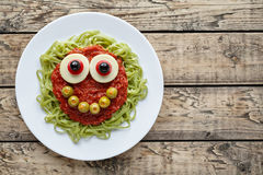 Green spaghetti pasta creative halloween food monster with cute smile and big mozzarella eyeballs Royalty Free Stock Photography